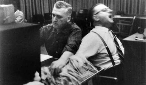 dva coveka sede, jedan drzi drugog za ruku i primenjuje elektrosokove (drugi glumi bol)