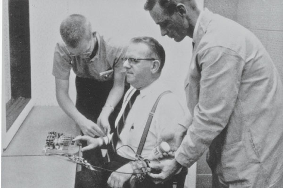 dva muskarca povezuju treceg sa tasterom za davanje elektrosokova