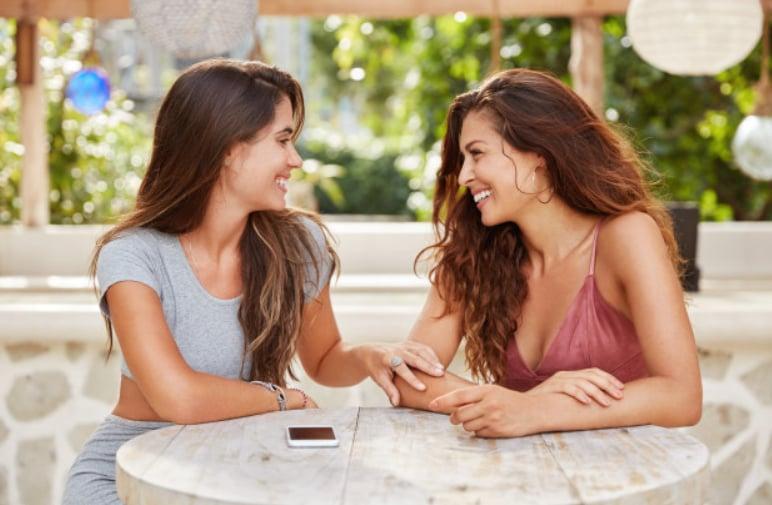 dve devojke sede i smeju se