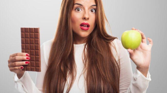 Devojka Zbunjena, Drzi Cokoladu U Jednoj, A Jabuku U Drugoj Ruci