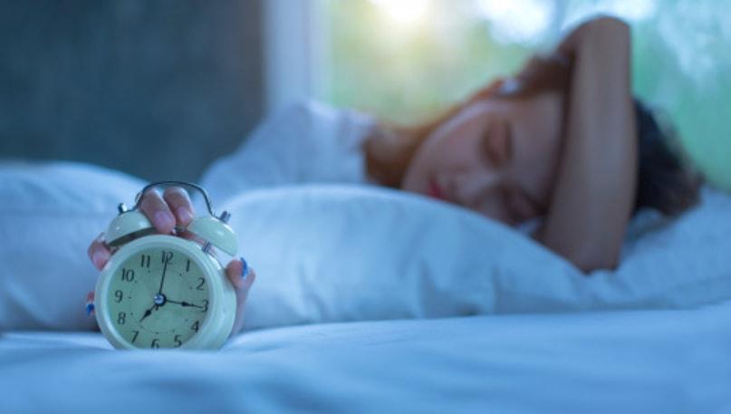 devojka u krevetu sa budilnikom u ruci
