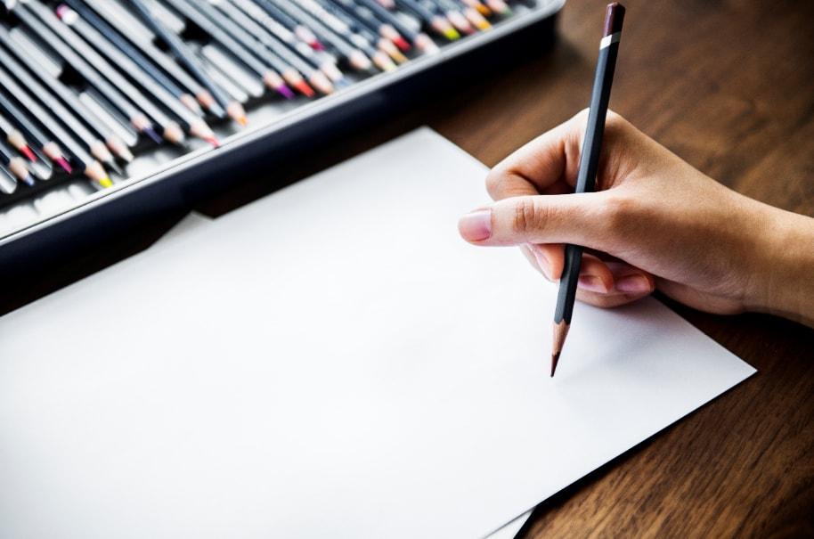 prazan papir i ruka koja drzi olovku za crtanje