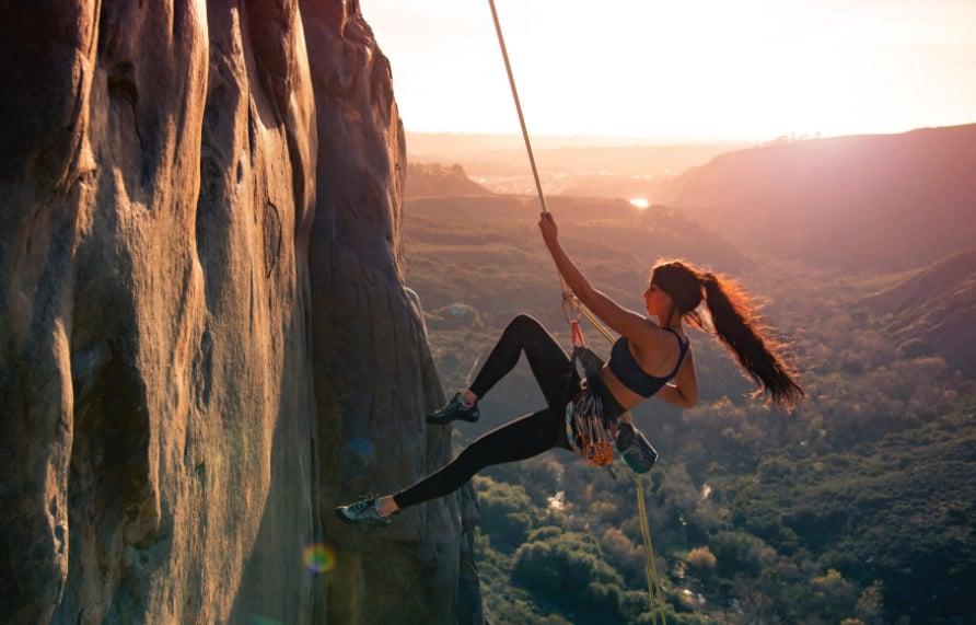 devojka planinari dok zalazi sunce
