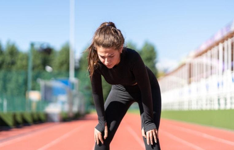 devojka na stazi za trcanje stoji zadihana