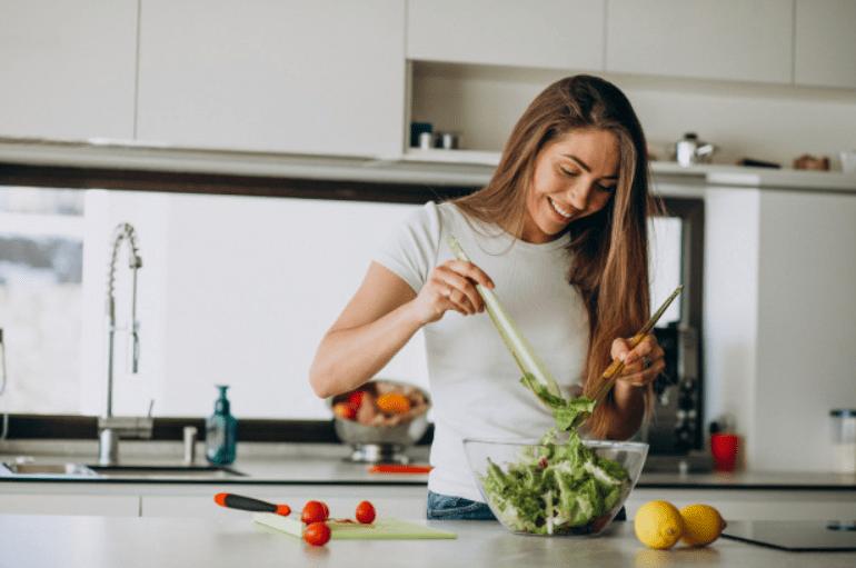 lepa nasmejana devojka pravi salatu u kuhinji
