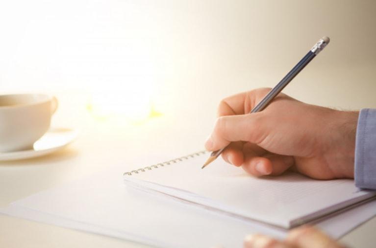 sveska i olovka na stolu, ruka koja pise