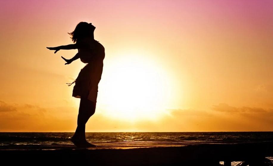 silueta zene rasirenih ruku uz zalazak sunca pored vode
