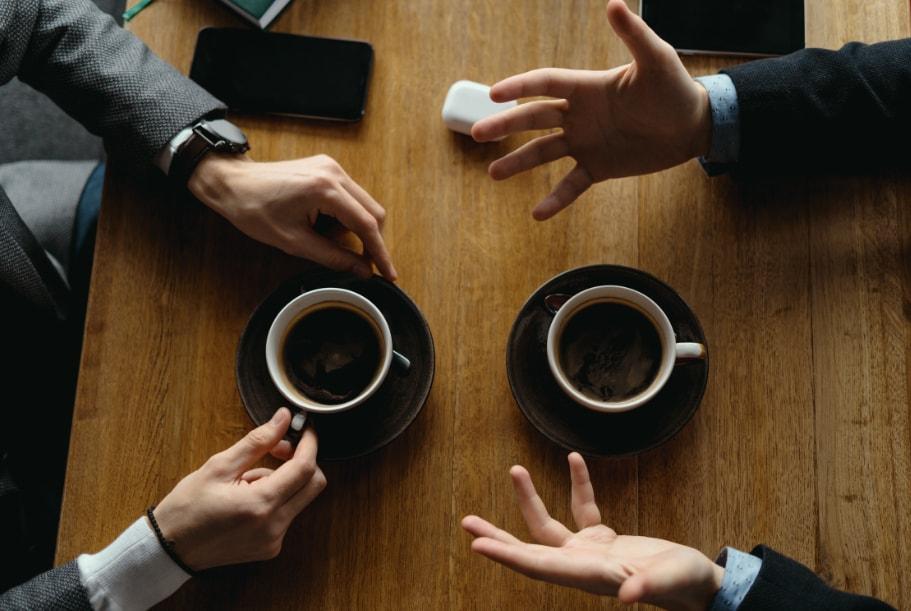 dlanovi dvojice muskaraca koji razgovaraju i dve kafe na stolu