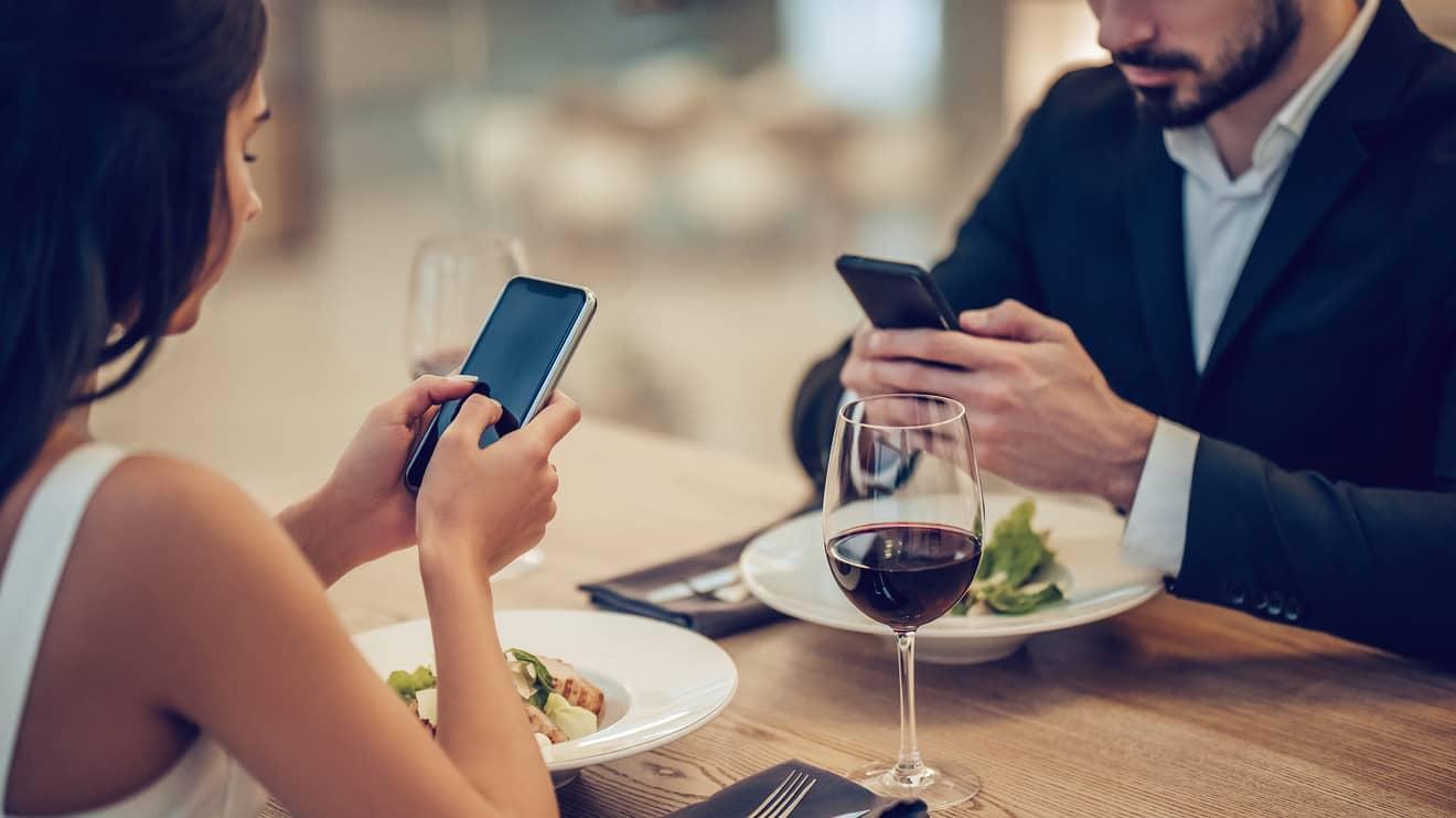 par sedi za stolom na veceri i oboje gledaju u telefone