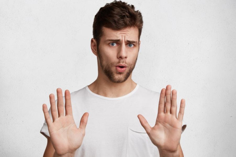momak drzi ruke u visini ramena, dlanove okrenute ka fotografu, u znak odbijanja