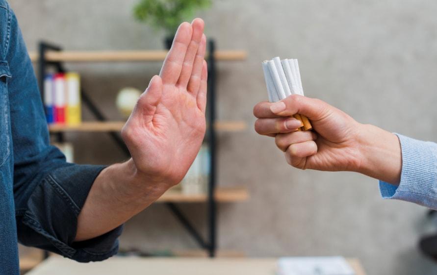 saka podignuta u znak odbijanja ka drugoj saci koja drzi cigarete