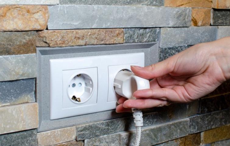 uticnica na zidu i ruka koja vadi kabl iz struje
