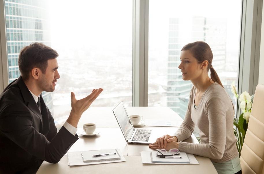 muskarac i zena sede jedno naspram drugog za stolom u kancelariji i razgovaraju