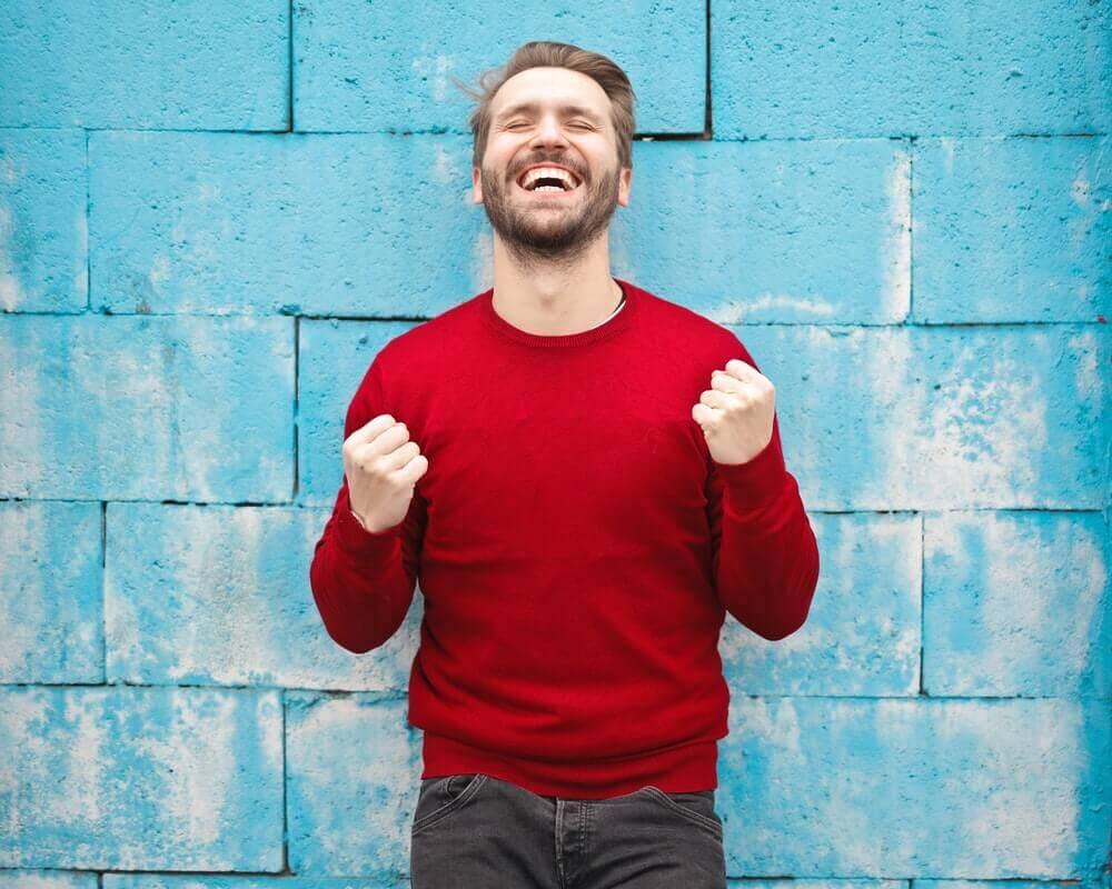srećan-čovek-plavi-zid-crveni-džemper